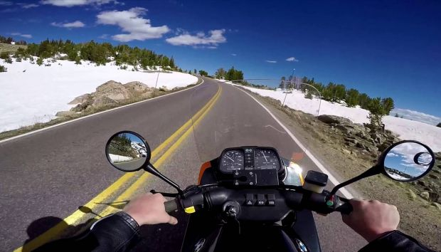 Riding a motorcycle in Beartooth Highway with snow in roadsides